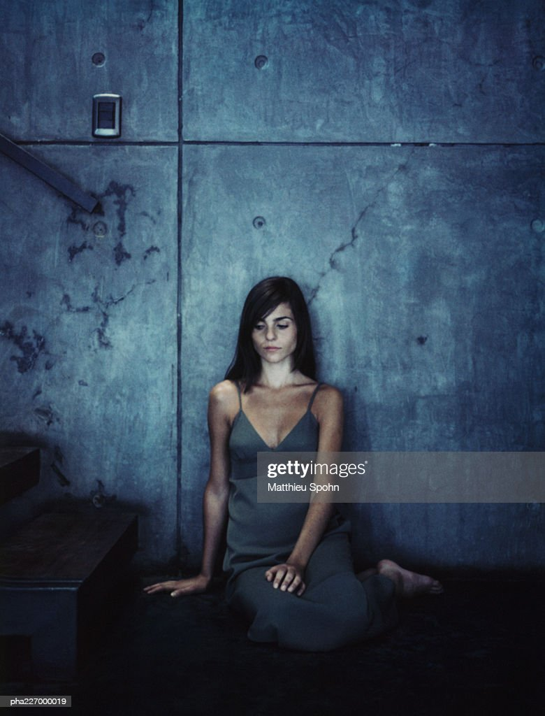 Woman sitting at bottom of stairs. : Stockfoto