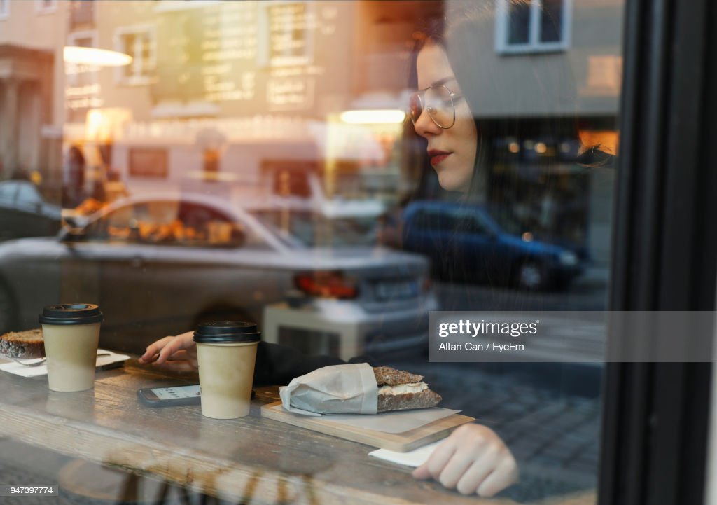 Woman Sitting At Cafe Seen Through Window : Stock Photo
