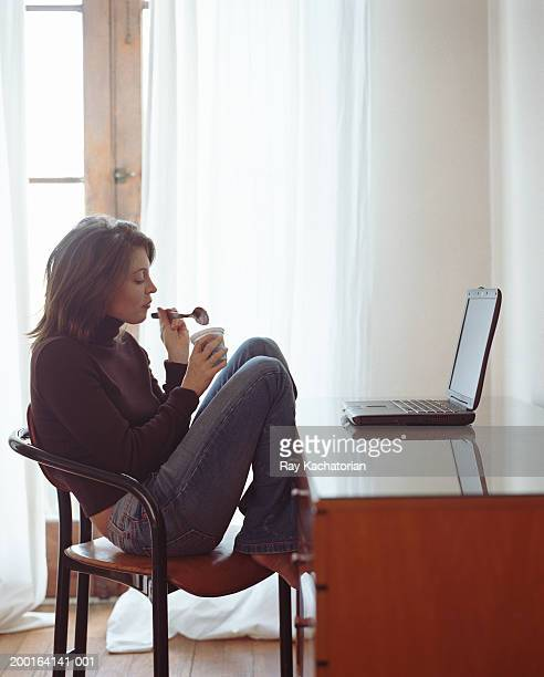 Woman sitting at computer desk with laptop, eating yogurt