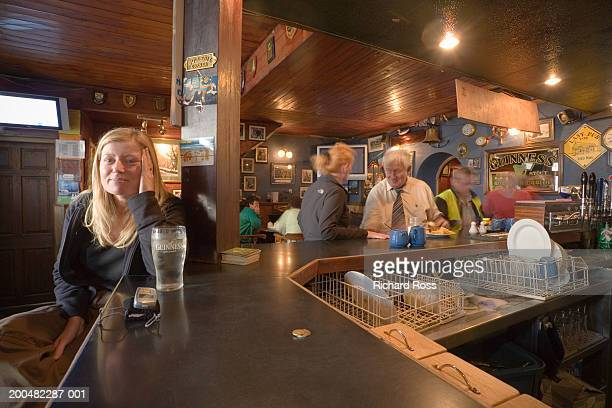 woman sitting at counter in bar - galway stock pictures, royalty-free photos & images