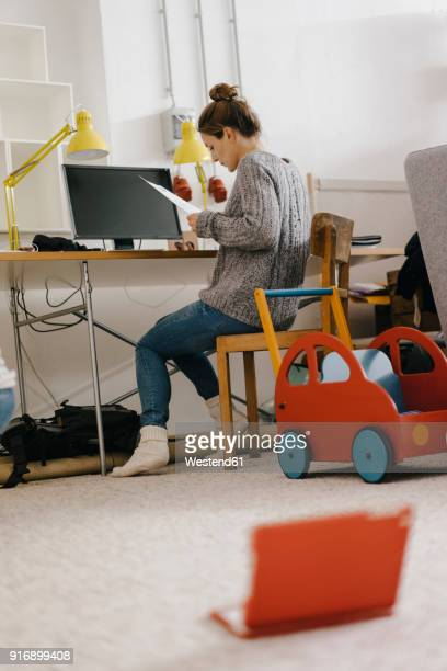 Woman sitting at desk at home surrounded by toys