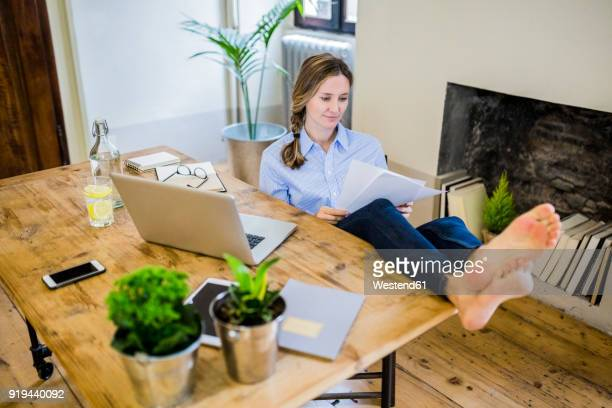 Woman sitting at desk at home with feet up reading document