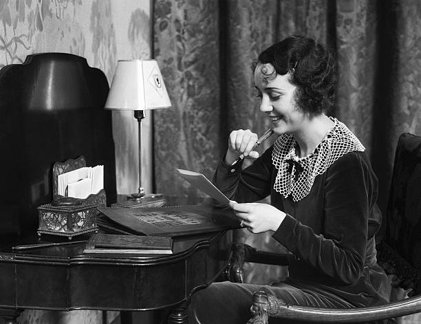 Woman sitting at desk at home, writing a letter.