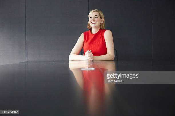 Woman sitting at desk hands together smiling