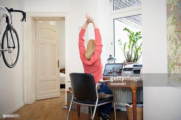 woman sitting at desk in her workroom stretching - dehnen stock-fotos und bilder