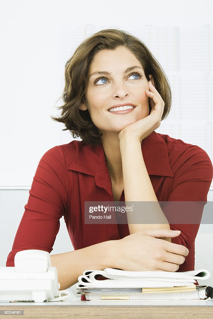 Woman sitting at desk in office, : Stock Photo