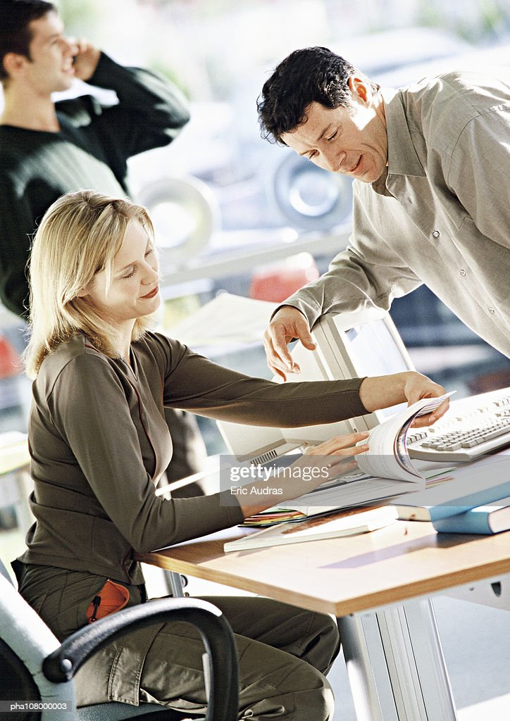 Woman sitting at desk looking at document, man leaning toward her. : Stockfoto