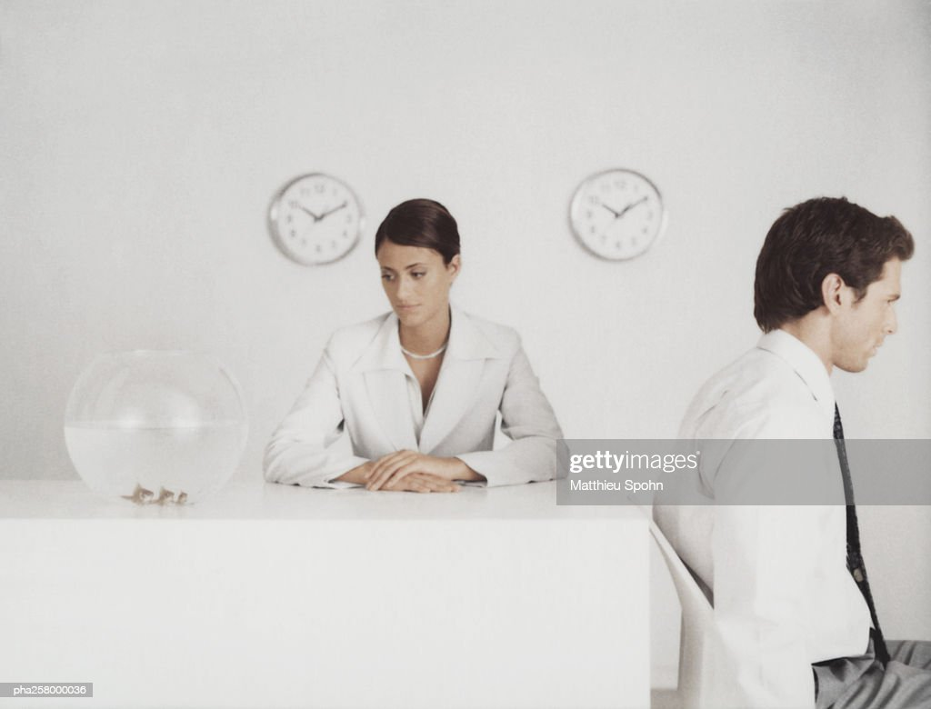 Woman sitting at desk looking at fishbowl, man sitting with back to desk : Stockfoto