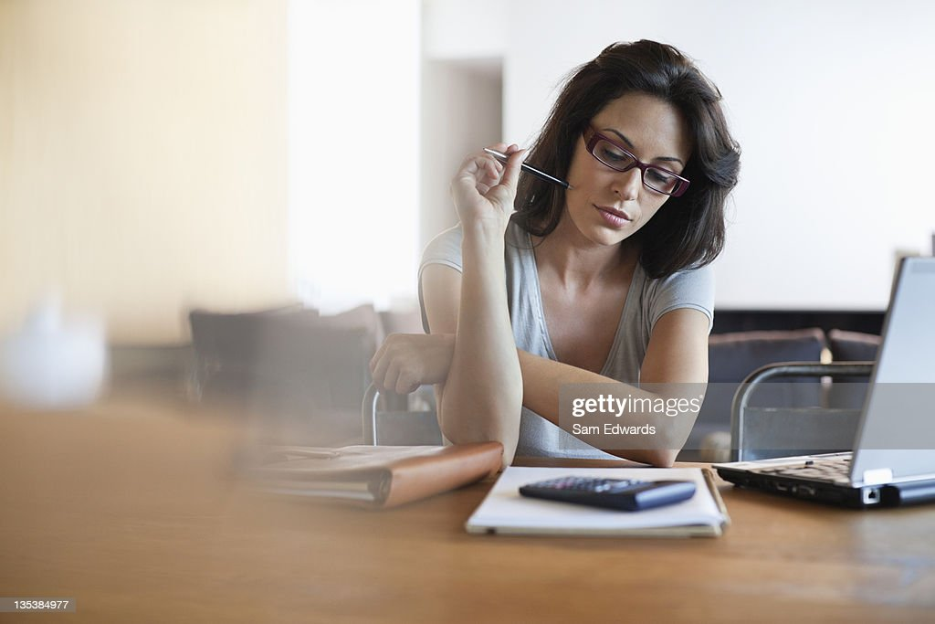 Woman sitting at desk looking at notebook : Stock Photo