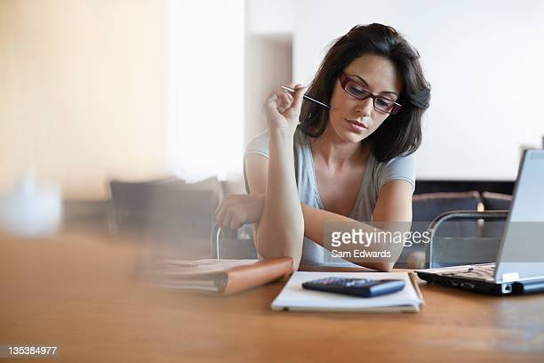 woman sitting at desk looking at notebook - calculator stock photos and pictures