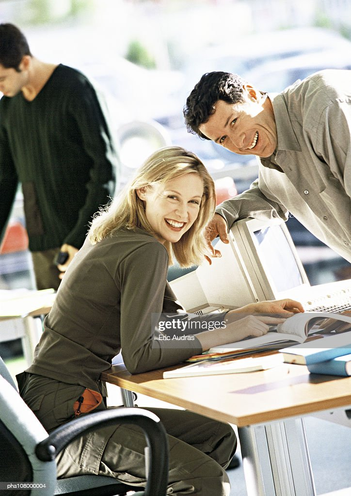 Woman sitting at desk, man leaning over desk, both smiling at camera : Stockfoto