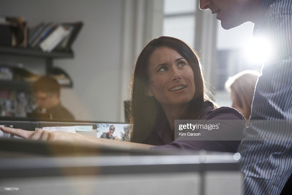 Woman sitting at desk talking to man at office (lens flare) : Stock Photo