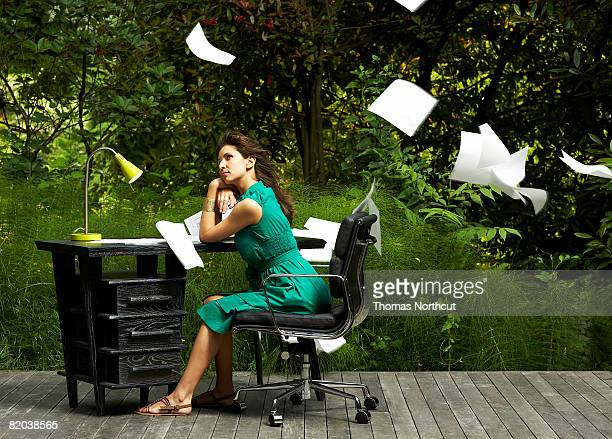 Woman sitting at desk with papers flying