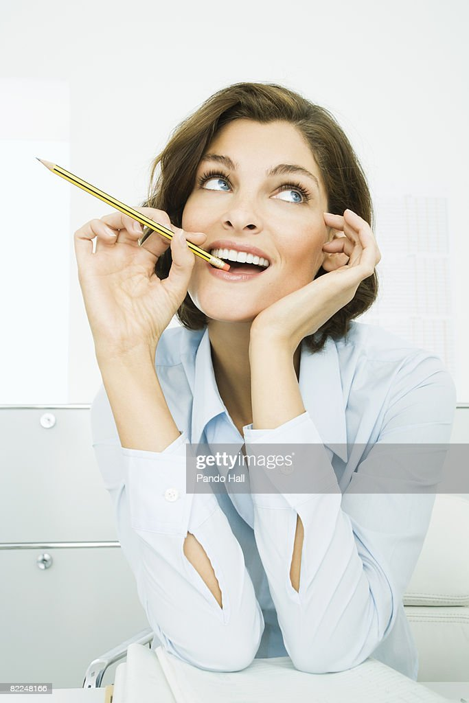 Woman sitting at desk with pencil in mouth : Stock Photo