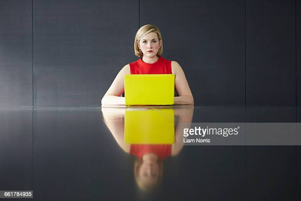 Woman sitting at desk with yellow laptop looking at camera