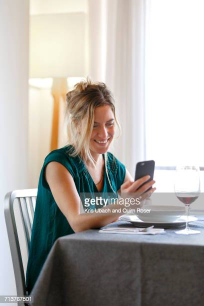 Woman sitting at diner table, using smartphone, smiling
