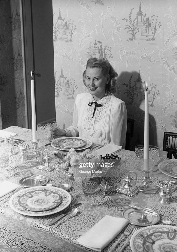 Woman sitting at dining room table, portrait : Stock Photo