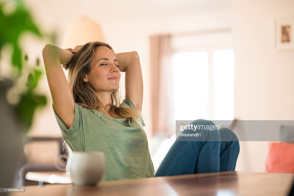 Woman sitting at dining table at home relaxing : Foto de stock