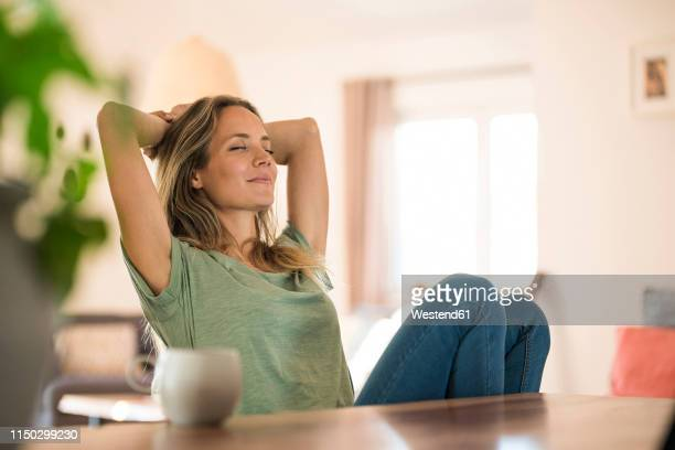 woman sitting at dining table at home relaxing - tevreden stockfoto's en -beelden