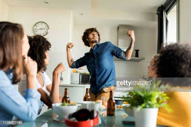 woman sitting at dining table watching man posing - flexing muscles stock pictures, royalty-free photos & images