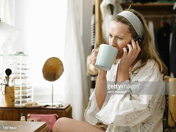 Woman sitting at dressing table using cell phone, while drinking from cup