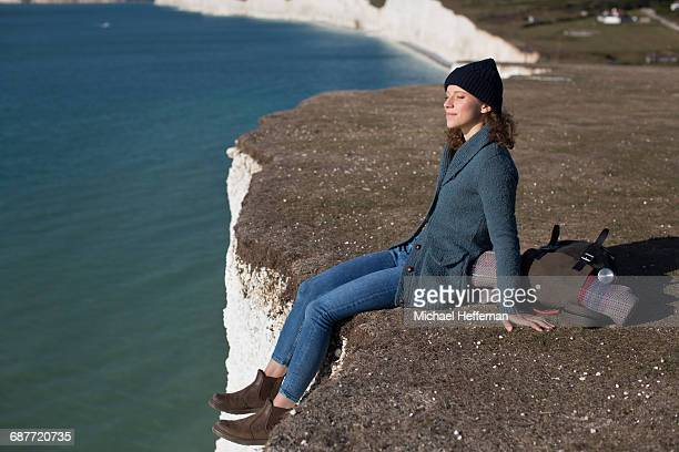 Woman sitting at edge of cliff