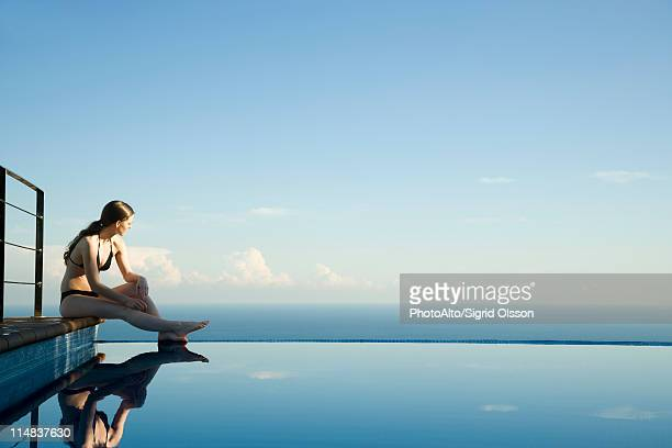 woman sitting at edge of infinity pool, looking at view - infinity pool foto e immagini stock