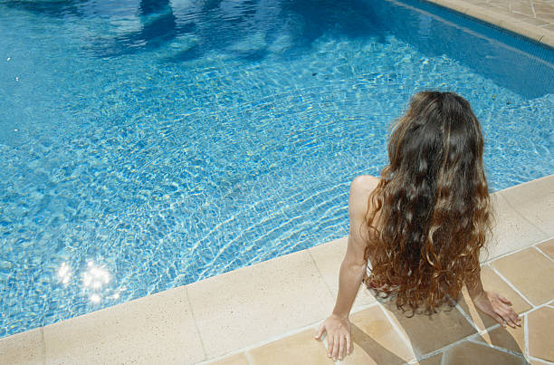 Woman sitting at edge of pool, rear view