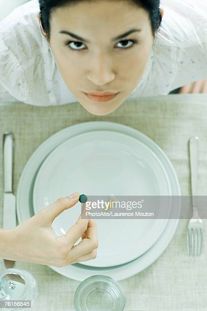 'Woman sitting at empty plate holding vitamin, looking up at camera'