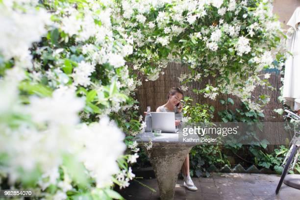 woman sitting at garden table with laptop, enjoying her lush outdoors office - jasmin bildbanksfoton och bilder