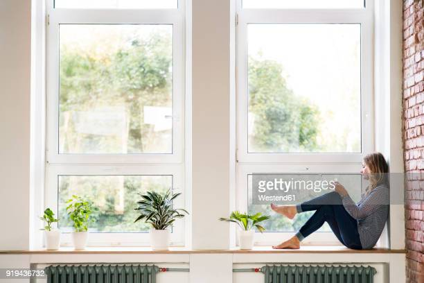 Woman sitting at home on the window sill, drinking coffee