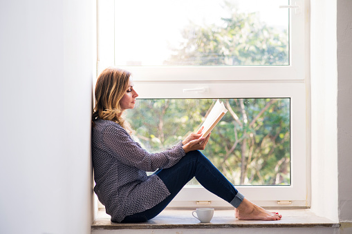 Woman sitting at home on the window sill, reading a book - gettyimageskorea