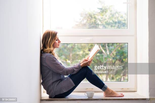 woman sitting at home on the window sill, reading a book - reading stock pictures, royalty-free photos & images