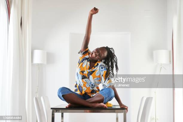 woman sitting at home table making triumph gesture - hand raised stock pictures, royalty-free photos & images