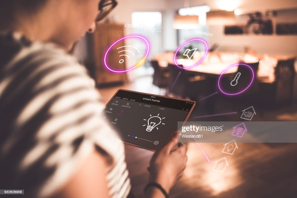 Woman sitting at home, using digital tablet to remote-control his smart home : Stock Photo
