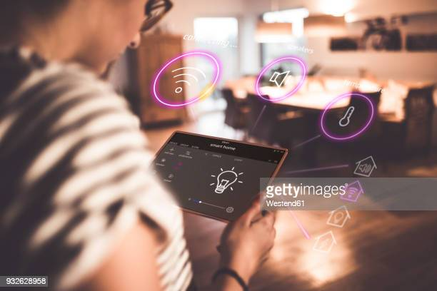 woman sitting at home, using digital tablet to remote-control his smart home - house icon stock pictures, royalty-free photos & images