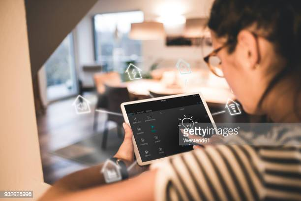 woman sitting at home, using digital tablet to remote-control his smart home - home icon stock photos and pictures