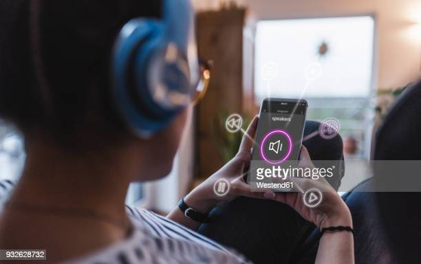 woman sitting at home with headphones, using smartphone as remote control - home icon stock photos and pictures