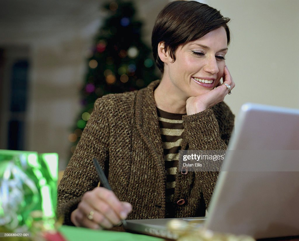 Woman sitting at laptop, resting chin on hand, smiling, focus on woman : Stock Photo