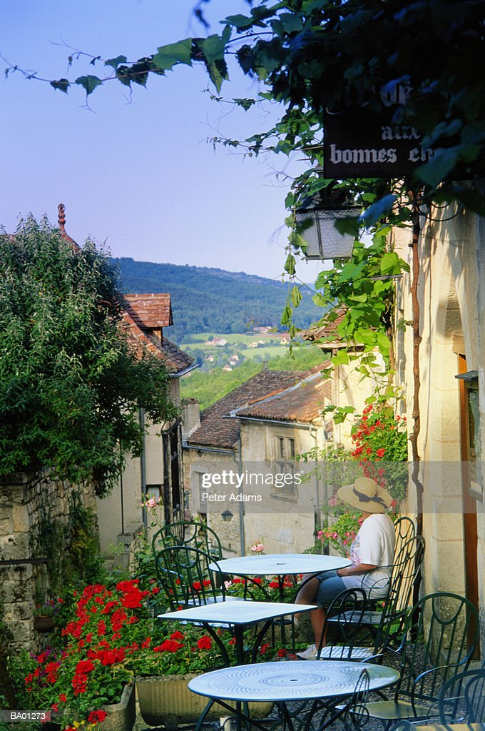 Woman sitting at outdoor cafe overlooking village, elevated view : Stock Photo