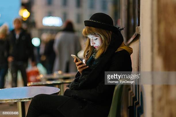 Frau sitzend im Café im Freien mit Cellphone