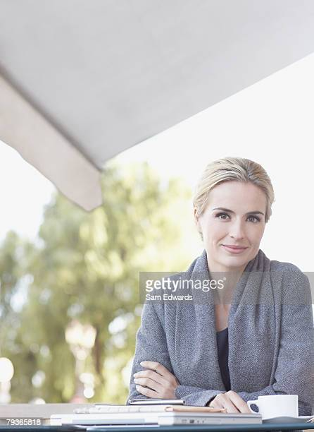 Woman sitting at outdoor patio table with notebook