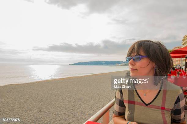 Woman Sitting at Restaurant by the Beach Against Cloudy Sky with Sunshine