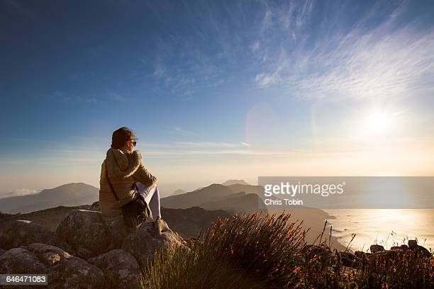 woman sitting at sunset on table mountain - table mountain stock pictures, royalty-free photos & images