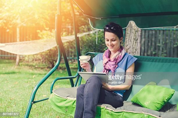 Mujer sentada en el desarrollo y el uso de tablet