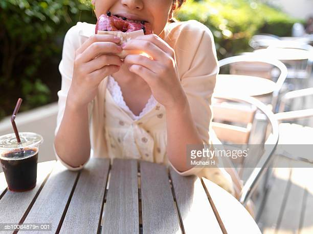 Woman sitting at table in cafe, eating donut, mid section
