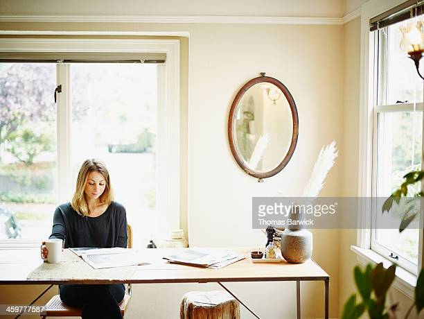Woman sitting at table in home reading newspaper