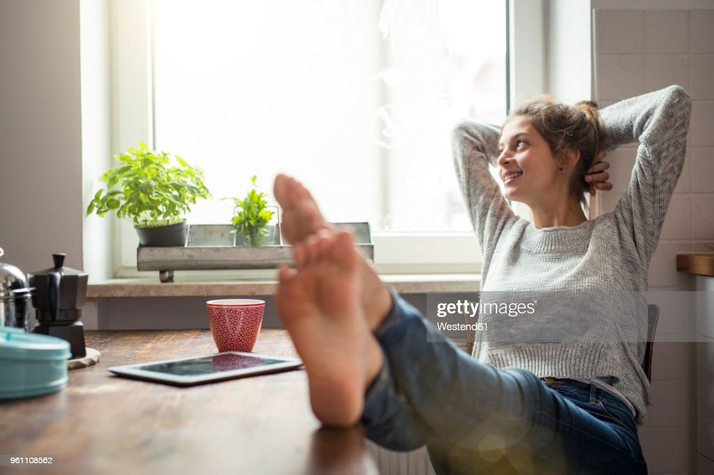 Woman sitting at table in kitchen relaxing : Stock Photo