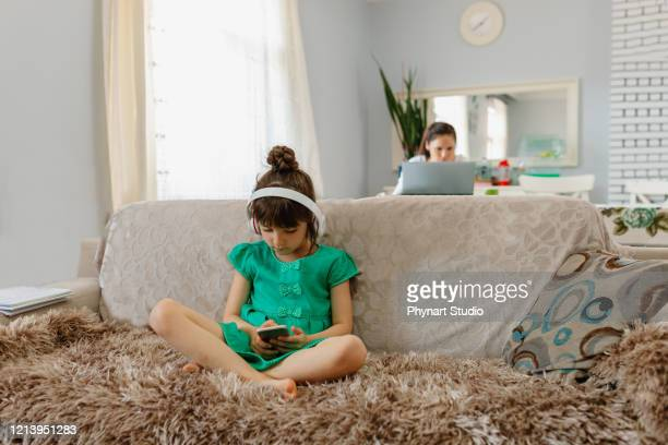 woman sitting at table in room. while her daughter was taking care of the phone,she is working from home because of epidemic - social distancing stock pictures, royalty-free photos & images