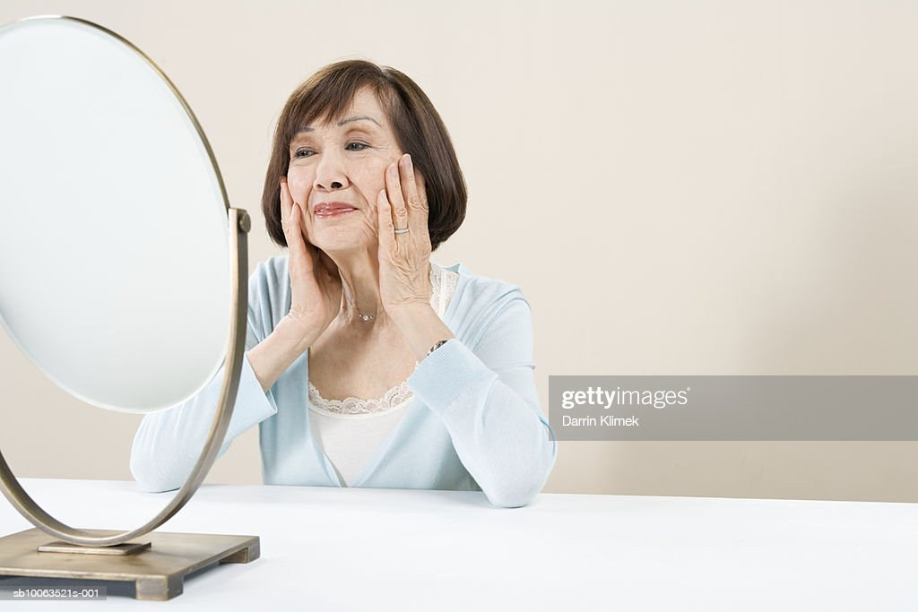 Woman sitting at table looking in mirror : Stock Photo